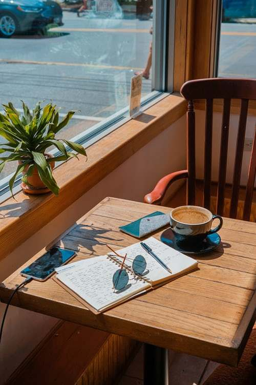 diary with lots of writing, a mobile phone and coffee in the sunshine