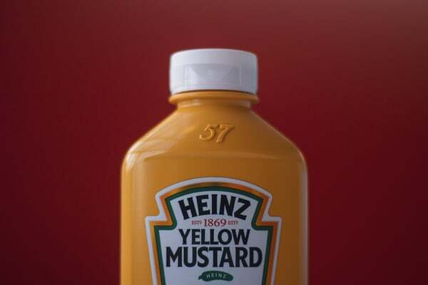 bottle of heinz yellow mustard with their well known branding and label
