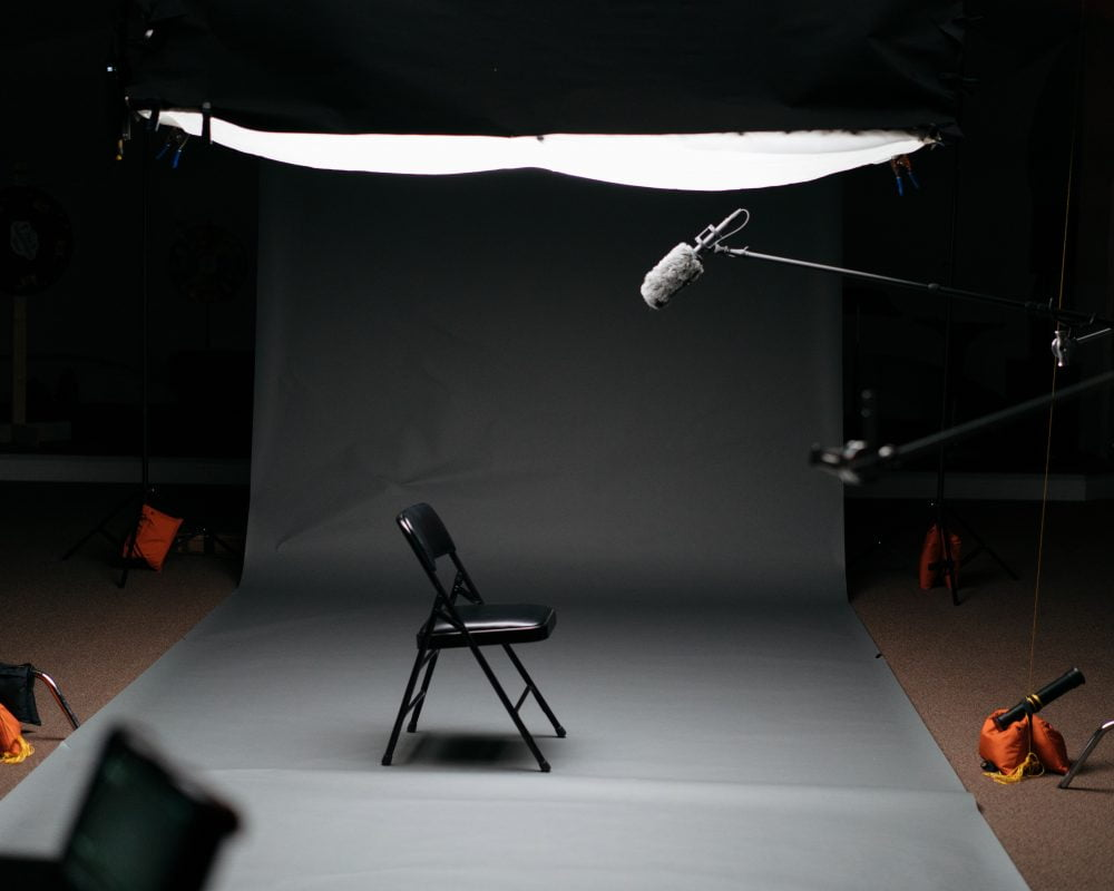 recording studio set up for video marketing content with chair, microphones and video cameras against a grey backdrop