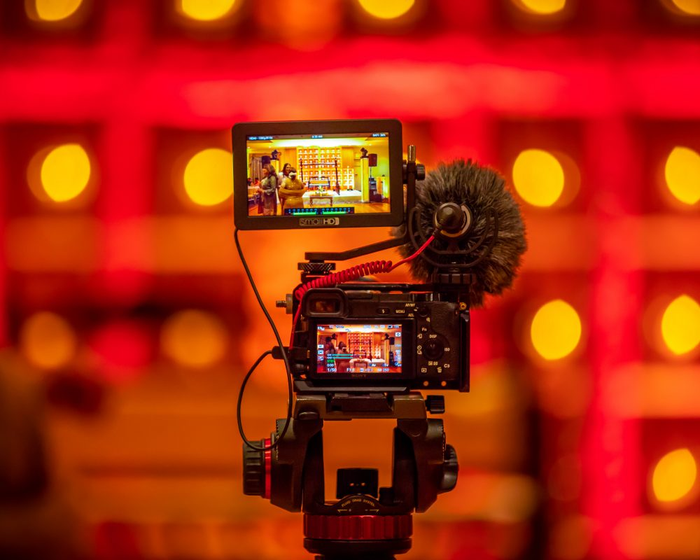 camera and video camera set up to record a marketing video with dramatic red backdrop