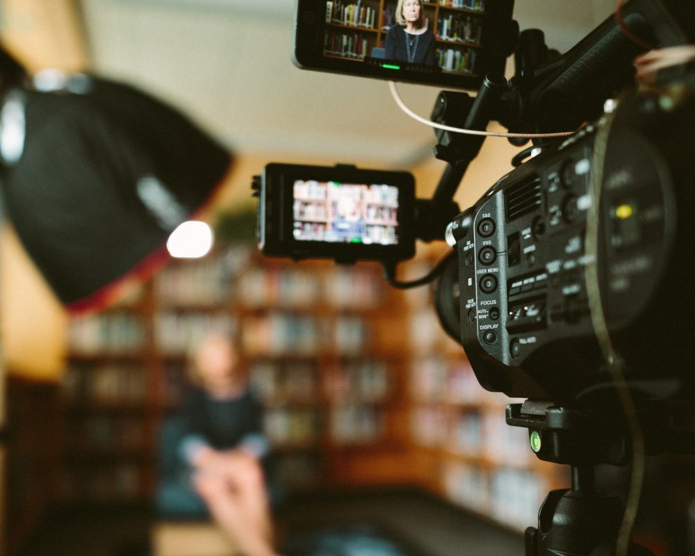Lady seated in library and camera focussed on her ready to record a marketing video