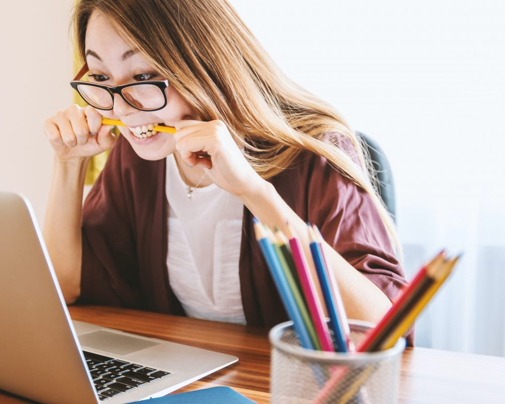 Frustrated woman writing headlines for blogs at her laptop